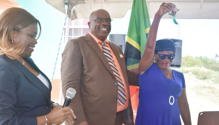 Ms Winfred O'Loughlin proudly displays the keys she received from Prime Minister Harris. On the left is Ms Myrtilla Williams of the Department of People Empowerment