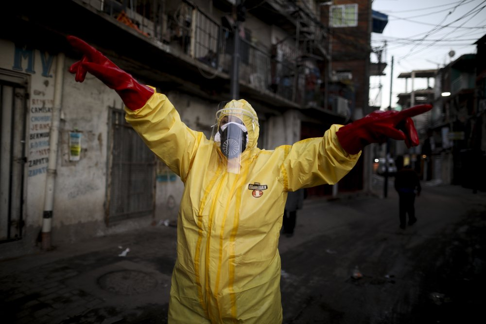 """In this Aug. 24, 2020 file photo, a student, wearing a face mask and shield, returns to the Melpark Primary School in Johannesburg after several months of lockdown. Ordinarily, South Africa sees widespread influenza during the winter months, but this year almost none have been found — something unprecedented. School closures, limited public gatherings and calls to wear masks and wash hands have """"knocked down the flu,"""" said Dr. Cheryl Cohen, head of the institute's respiratory program. (AP Photo/Denis Farrell, File)"""