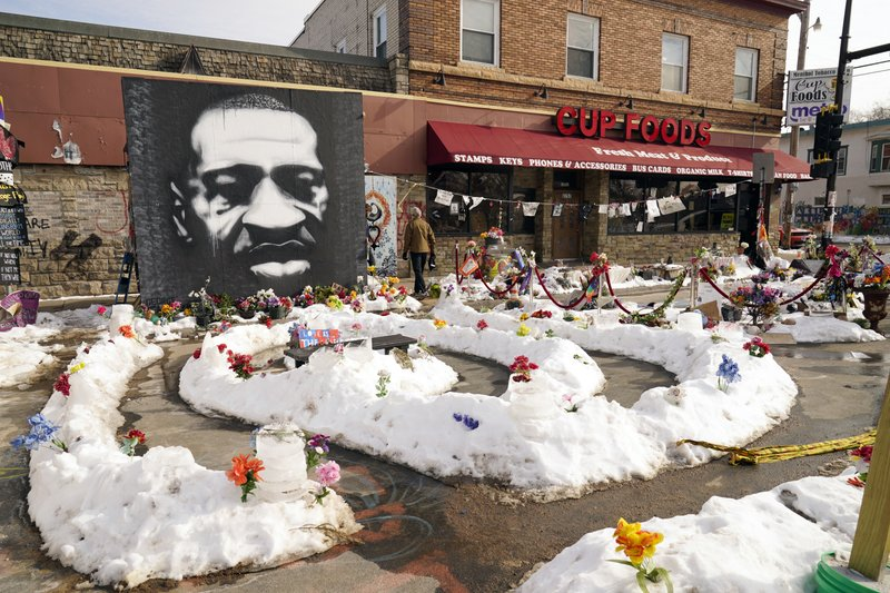 FILE – In this Feb. 8, 2021 file photo, A mural of George Floyd is seen in George Floyd Square in Minneapolis. The city of Minneapolis on Friday, March, 12, 2021, agreed to pay $27 million to settle a civil lawsuit from George Floyd's family over the Black man's death in police custody, as jury selection continued in a former officer's murder trial. The settlement includes $500,000 for the south Minneapolis neighborhood that includes the 38th and Chicago intersection that has been blocked by barricades since his death, with a massive metal sculpture and murals in his honor. (AP Photo/Jim Mone File)